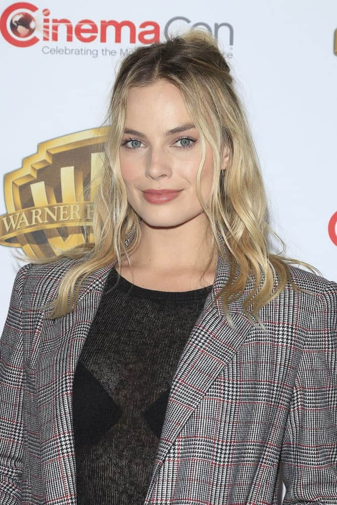 Margot Robbie attended the Warner Bros. Pictures Presentation during CinemaCon at Caesars Palace on April 12, 2016. She wore a gray check suit that complements her tousled half updo.
