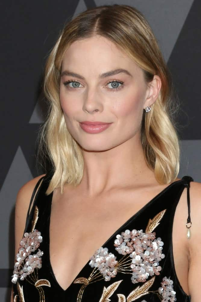 Margot Robbie in a black floral dress during the AMPAS 9th Annual Governors Awards at Dolby Ballroom on November 11, 2017. She paired it with a center-parted wavy hairstyle that's defined with blonde highlights.