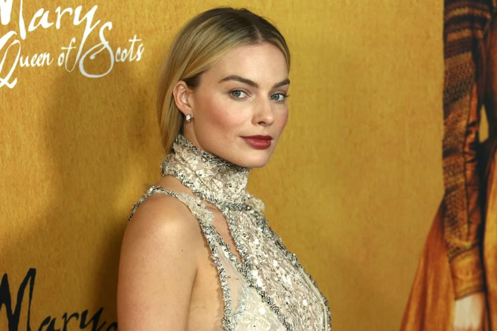 Margot Robbie gathered her blonde hair in a loose ponytail that emphasized her embellished halter dress at the