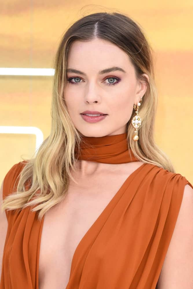 Margot Robbie looked stunningly gorgeous in a daring red dress that complements her loose waves with a middle parting and shadow roots. This was taken at the UK premiere for