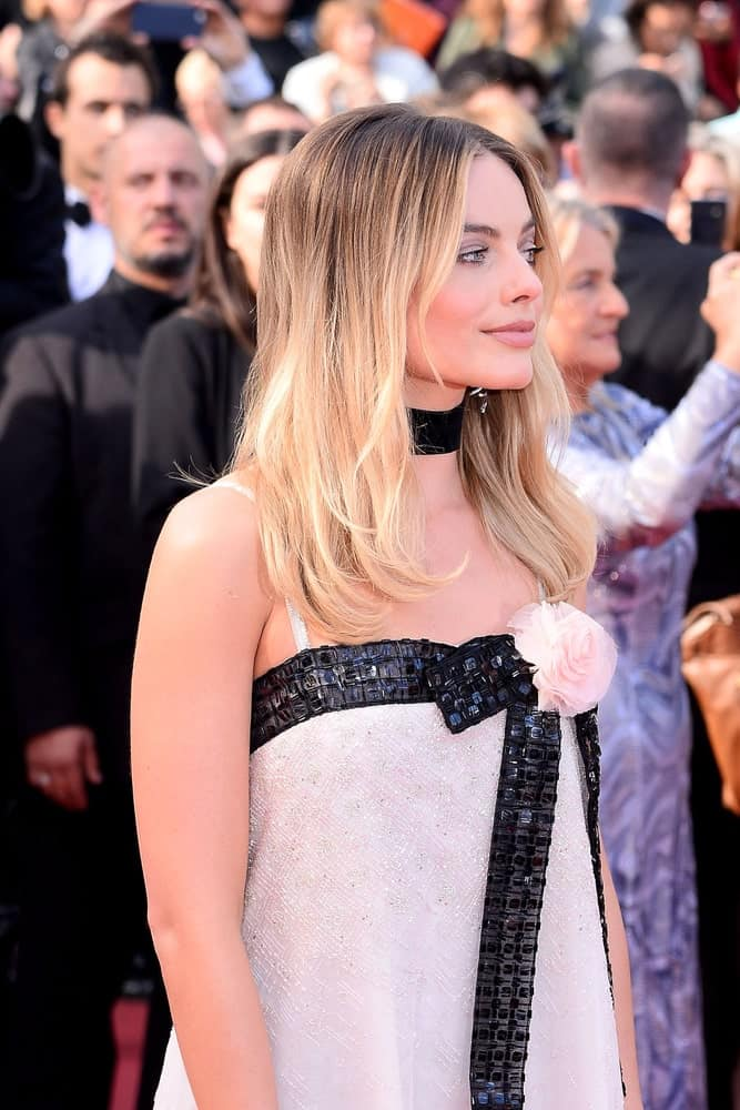 Margot Robbie shows off her straight blonde tresses with dark shadow roots at the Premiere of the film