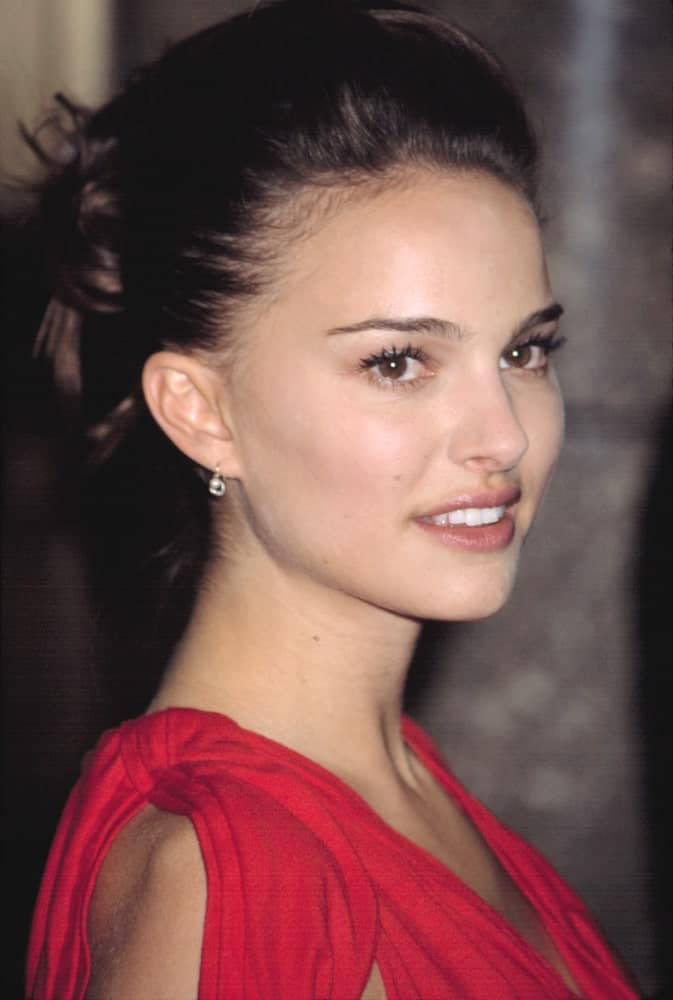 Natalie Portman went with a brushed-back pompadour look to her upstyle bun hairstyle with loose tendrils at the VH1 VOGUE FASHION AWARDS held in New York on October 15, 2002.