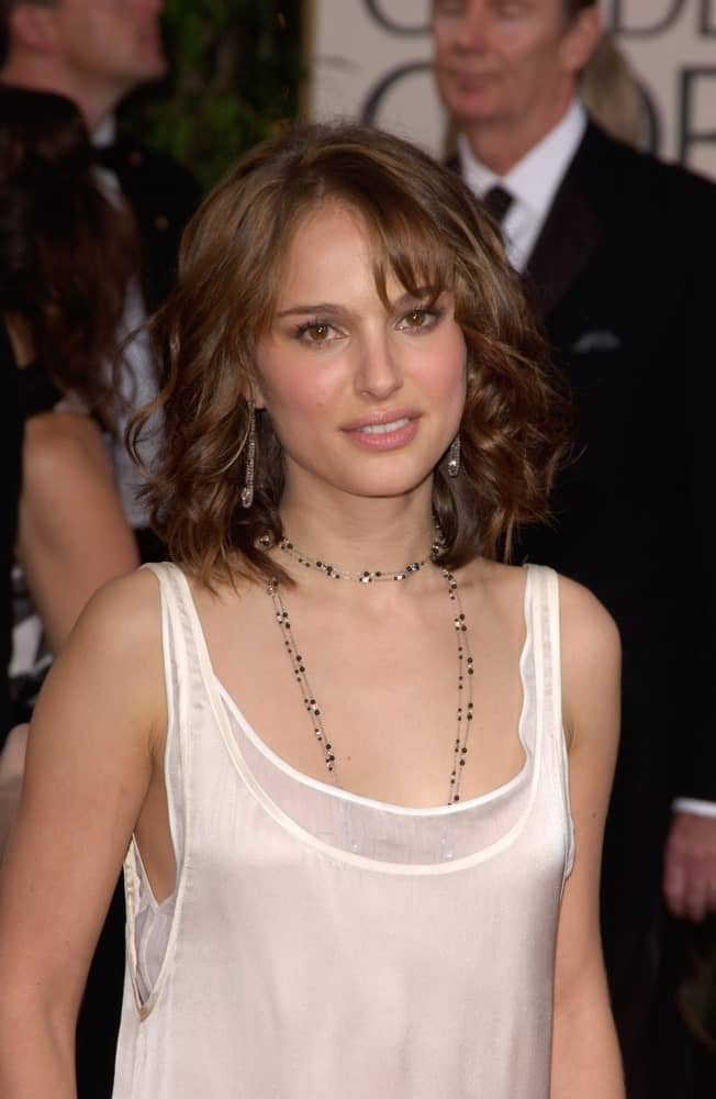 On January 16, 2005, Natalie Portman paired her carefree white casual dress with a tousled shoulder length hairstyle with curls, bangs and layers at the 62nd Annual Golden Globe Awards at the Beverly Hilton Hotel.
