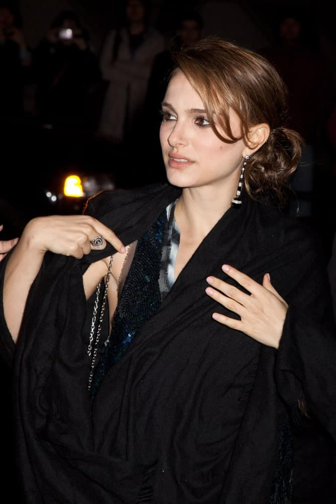 On November 30, 2009, actress Natalie Portman attended the IFP's 19th Annual Gotham Independent Film Awards at Cipriani, Wall Street. She wore a large black coat to match her messy low bun hairstyle with loose tendrils and side-swept bangs.