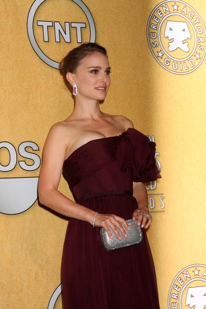 Natalie Portman wore a strapless maroon dress that she paired with a lovely silver purse and slick side-swept upstyle bun in the Press Room at the 18th Annual Screen Actors Guild Awards at Shrine Auditorium on January 29, 2012 in Los Angeles, CA.