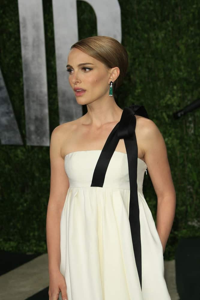 Natalie Portman's brown highlighted hair was swept up into a slick and neat upstyle to go with her white dress at the Vanity Fair Oscar Party at Sunset Tower on February 24, 2013 in West Hollywood, California.