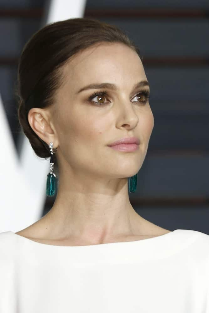 Natalie Portman's slick low bun hairstyle was perfectly matched with her green earrings and white dress at the Vanity Fair Oscar Party 2015 at the Wallis Annenberg Center for the Performing Arts on February 22, 2015 in Beverly Hills, CA.