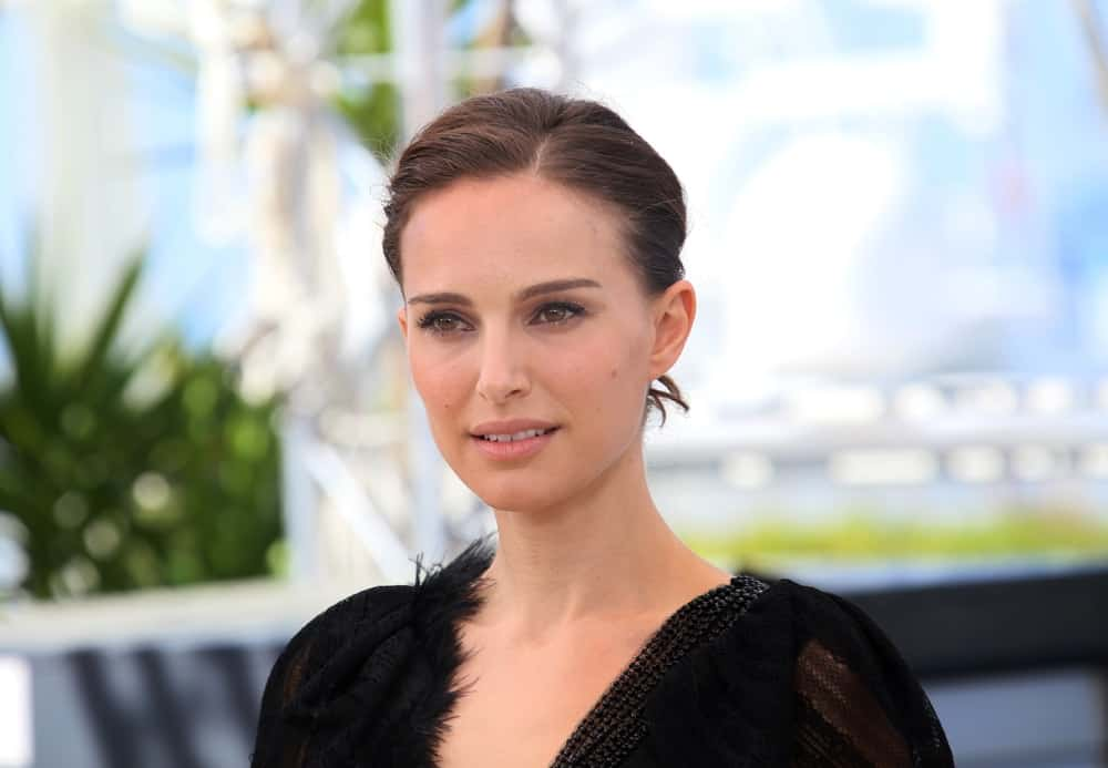 Natalie Portman went with a simple look to her dark upstyle bun hair that matched perfectly well with her sheer black dress at the 'A Tale Of Love And Darkness' photocall during the 68th annual Cannes Film Festival on May 17, 2015 in Cannes, France.