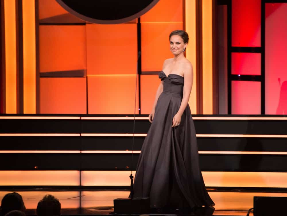 On November 10, 2017, Natalie Portman was at the American Cinematheque 2017 Award Show at the Beverly Hilton Hotel. She wore an elegant charcoal strapless dress to match her neat upstyle bun.