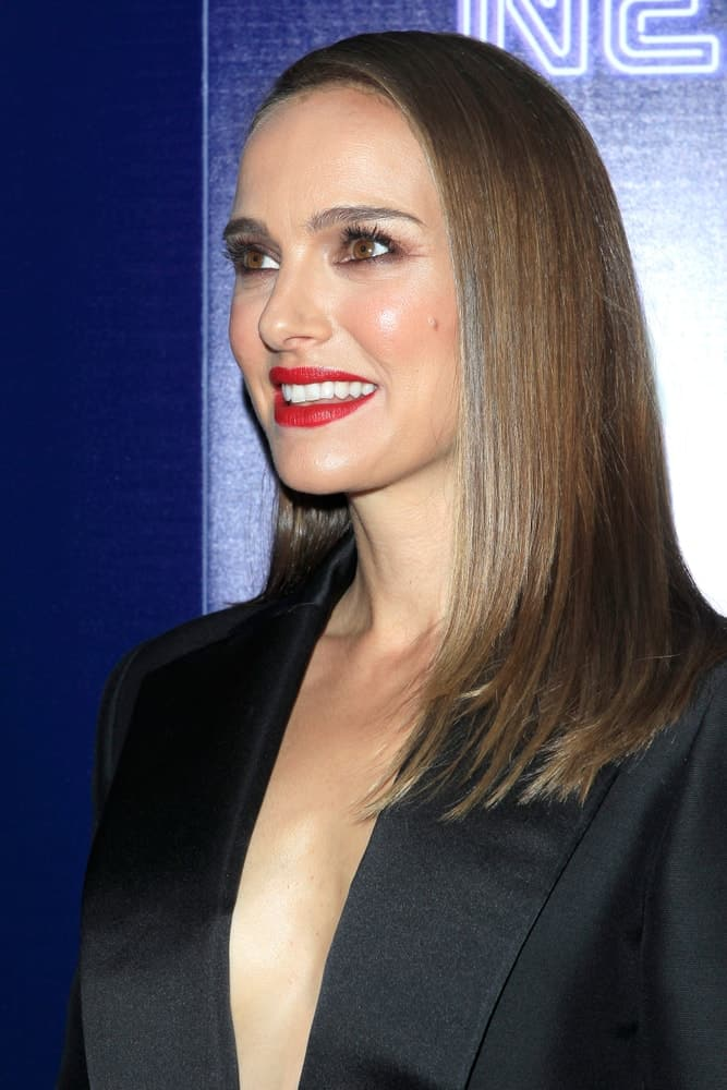 Natalie Portman paired her bold red lips and stunning black dress with a straight side-swept hairstyle that has highlights at the
