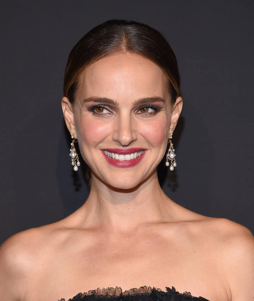Natalie Portman's elegant make-up and earrings went perfectly well with her strapless black dress and slick highlighted bun hairstyle when she arrived for the ELLE Women in Hollywood on October 14, 2019 in Westwood, CA.