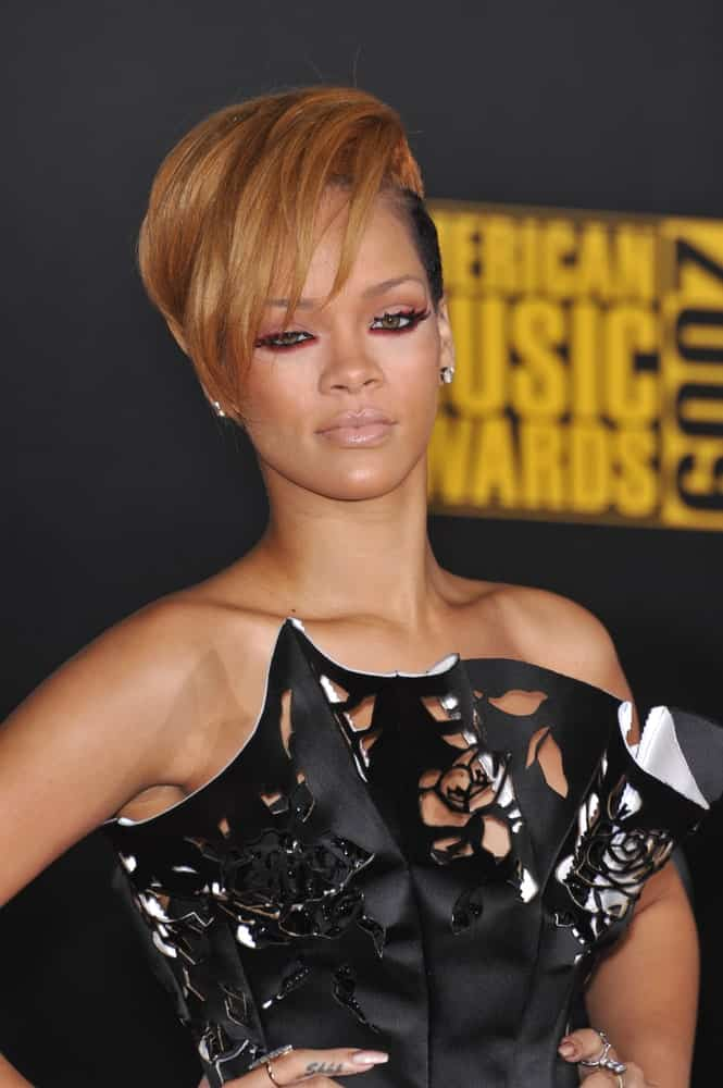Rihanna wore an artistic and fashionable black dress with her light brown pixie hairstyle incorporated with long side-swept bangs at the 2009 American Music Awards at the Nokia Theatre L.A. Live on November 22, 2009.
