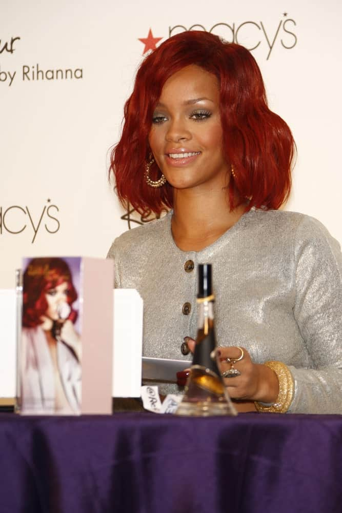 Rihanna was at Macy's in Lakewood, California at the launch of her first fragrance 'Reb'l Fleur' on February 18, 2011. She was lovely in her gray outfit and shoulder-length red hairstyle with waves and tousles.