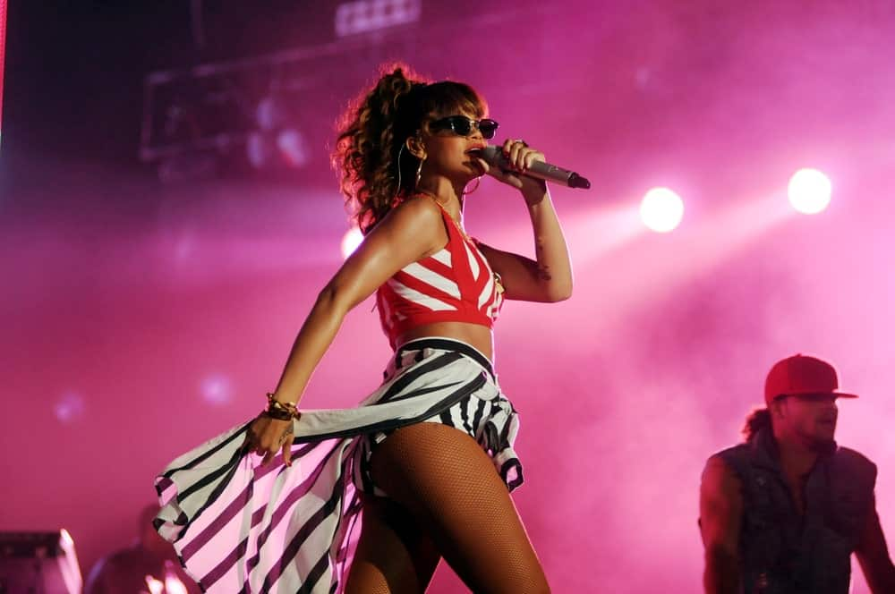 On September 11, 2011, Singer Rihanna rocked the stage during the Rock in Rio event. She was wearing a stylish two-piece outfit to go with her curly and highlighted high ponytail incorporated with bangs.