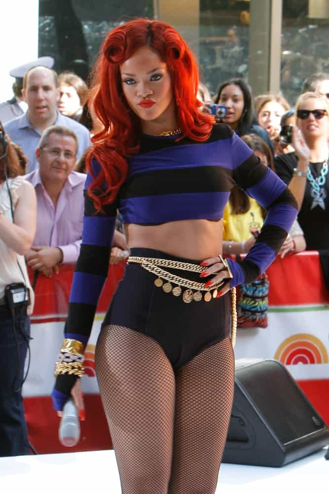 Singer Rihanna performed on the TODAY Show Concert Series at Rockefeller Plaza on May 27, 2011 in New York City. She was wearing a unique and fashionable ensemble outfit with her bright red long and loose hairstyle with vintage curls.