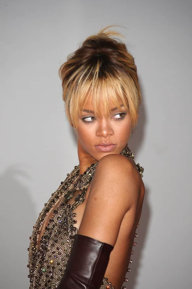 Rihanna was at the 2012 Brit Awards held at the O2 Arena in London on February 21, 2012. She paired her bejeweled dress with a messy bun hairstyle with highlights and loose wispy bangs.
