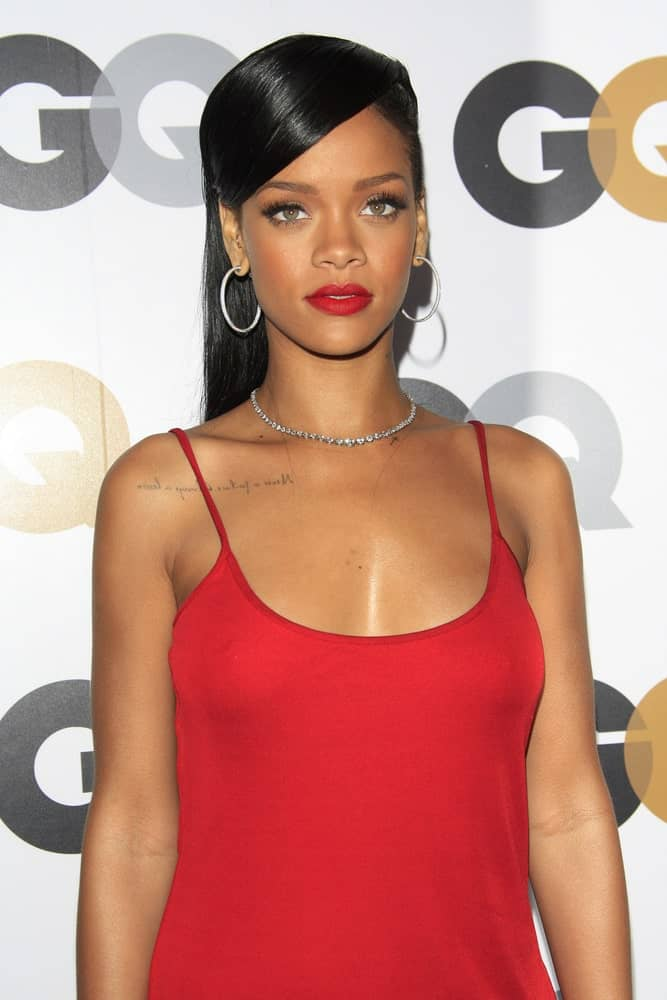 Rihanna arrived at the GQ Men Of The Year Party at Chateau Marmont Hotel on November 13, 2012 in Los Angeles, California. She was wearing a stunning red dress to pair with her long and straight raven hairstyle incorporated with pinned side-swept bangs.