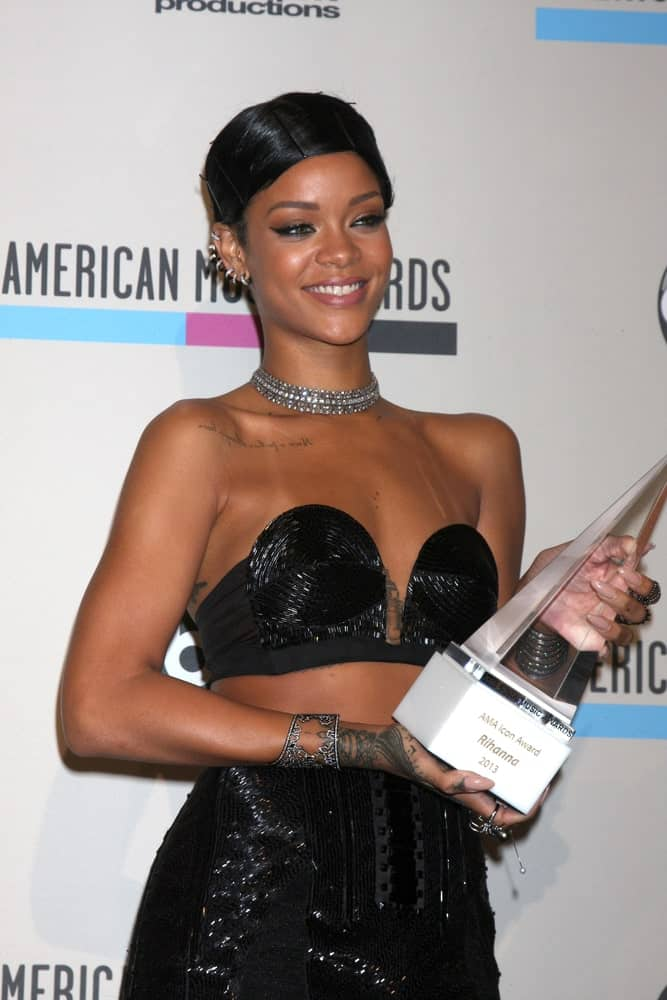 Rihanna was at the 2013 American Music Awards Press Room at Nokia Theater on November 24, 2013 in Los Angeles, CA. She wore an elegant shiny black dress that she topped with a raven slick upstyle.