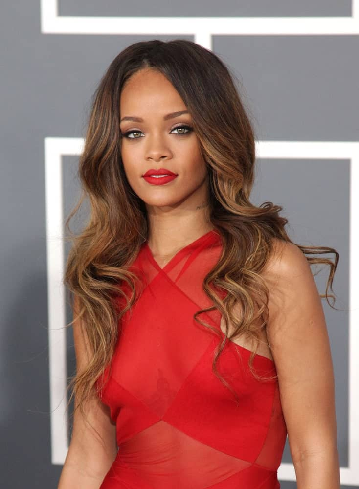 Rihanna stunned everyone with her sheer red dress that she paired with her long and wavy highlighted hair resting on her shoulders when she attended the Grammy Awards 2013 on February 10, 2013 in Los Angeles, CA.