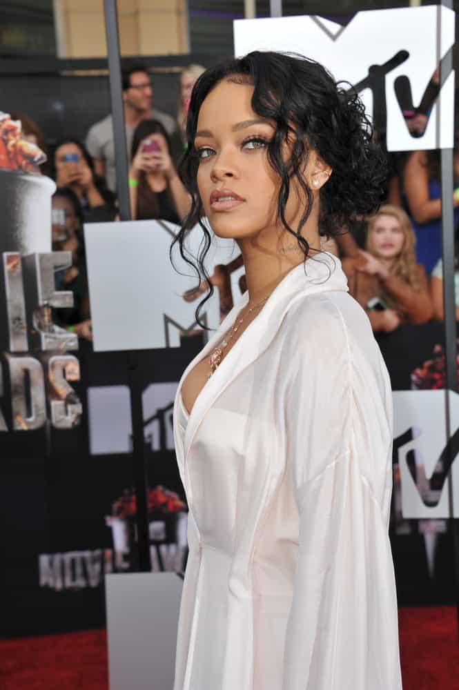 On April 13, 2014, Rihanna's long and curly raven hair was swept up into a messy low bun hairstyle with loose curly tendrils at the 2014 MTV Movie Awards at the Nokia Theatre LA Live.