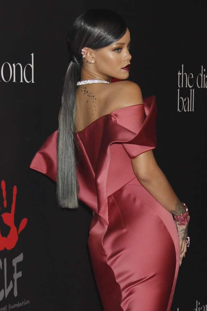 Rihanna was at the First Annual Diamond Ball at the The Vineyard on December 11, 2014 in Beverly Hills, CA. She wore a sexy form-hugging silk dress that paired well with her long straight hair with metallic highlights styled into a low ponytail.