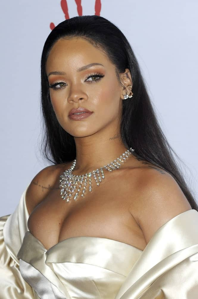 Rihanna wowed everyone with her stunning pearly white dress and slicked back long straight hairstyle at the 2nd Annual Diamond Ball held at the Barker Hanger in Santa Monica, USA on December 10, 2015.