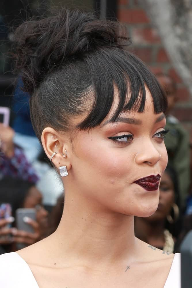 Rihanna's lovely dark lips matched well with her white outfit and top knot bun hairstyle with bangs at the