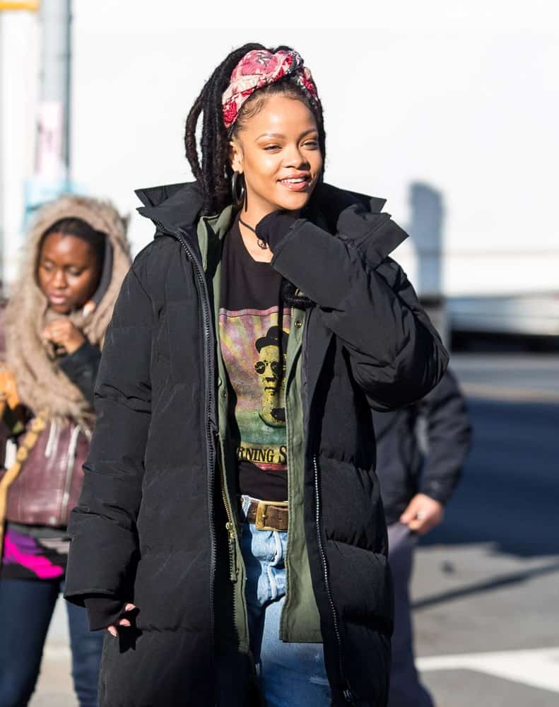 Rihanna was seen on December 5, 2016 walking the streets of New York City. She was wearing a large black winter jacket over her casual clothes and her hair was styled into long dreadlocks held up by a colorful headband.