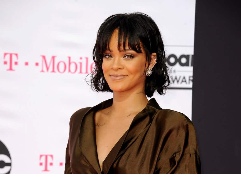 Rihanna was at the 2016 Billboard Music Awards held at T-Mobile Arena in Las Vegas, USA on May 22, 2016. Her simple dark brown outfit is complemented by her simple make-up and wavy tousled short hair with eye-skimmer bangs.