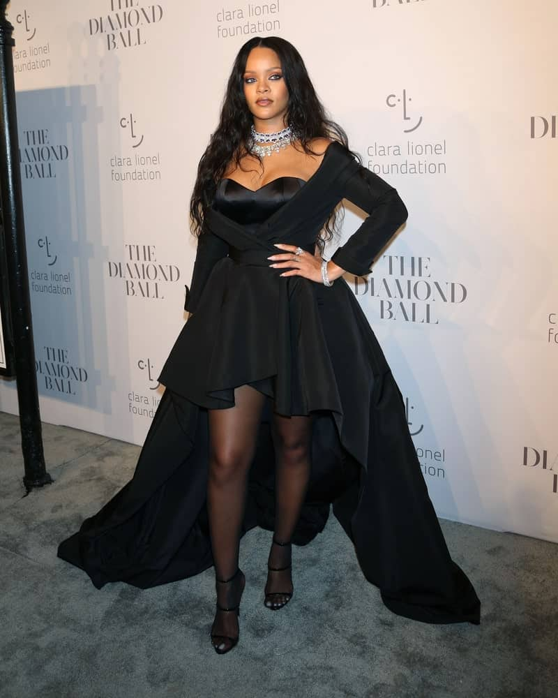 Rihanna went with a slight goth look in her pure black outfit and long tousled wavy raven hairstyle when she attended the 3rd annual Diamond Ball at Cipriani on September 14, 2017, in New York City.