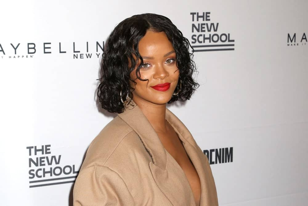 Rihanna attended the 69th annual Parsons Benefit at Chelsea Piers on May 22, 2017, in New York. She wore a fashionable brown dress that looks like a trench coat and paired this with her short and curly bob hairstyle.