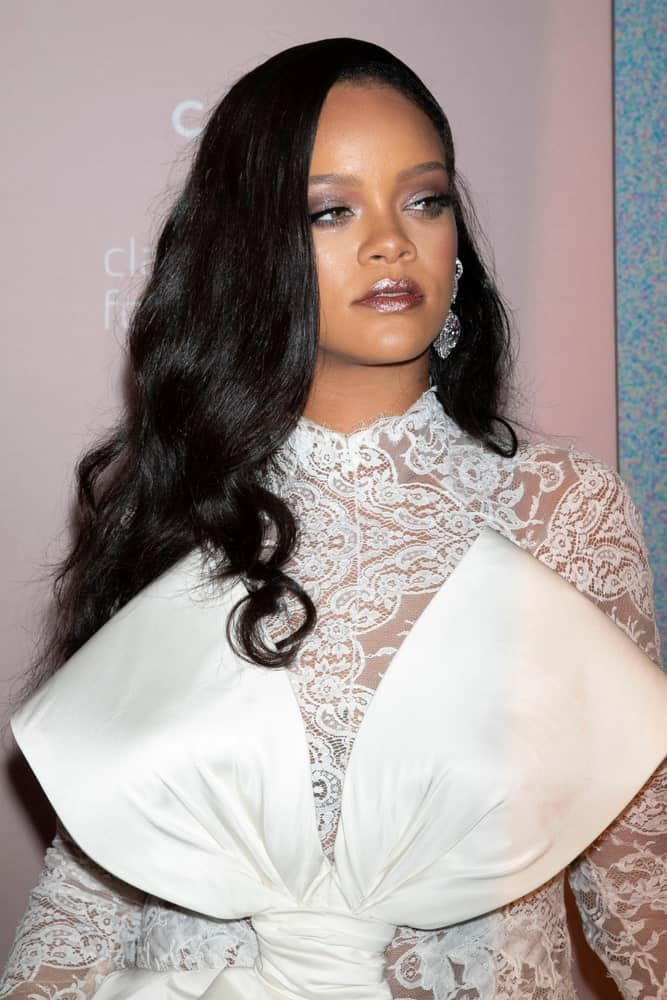 Rihanna's elegant and fashionable white sheer dress contrasts perfectly with her raven side-swept long hair with a wavy finish at the 4th annual Diamond Ball at Cipriani on September 13, 2018, in New York City.