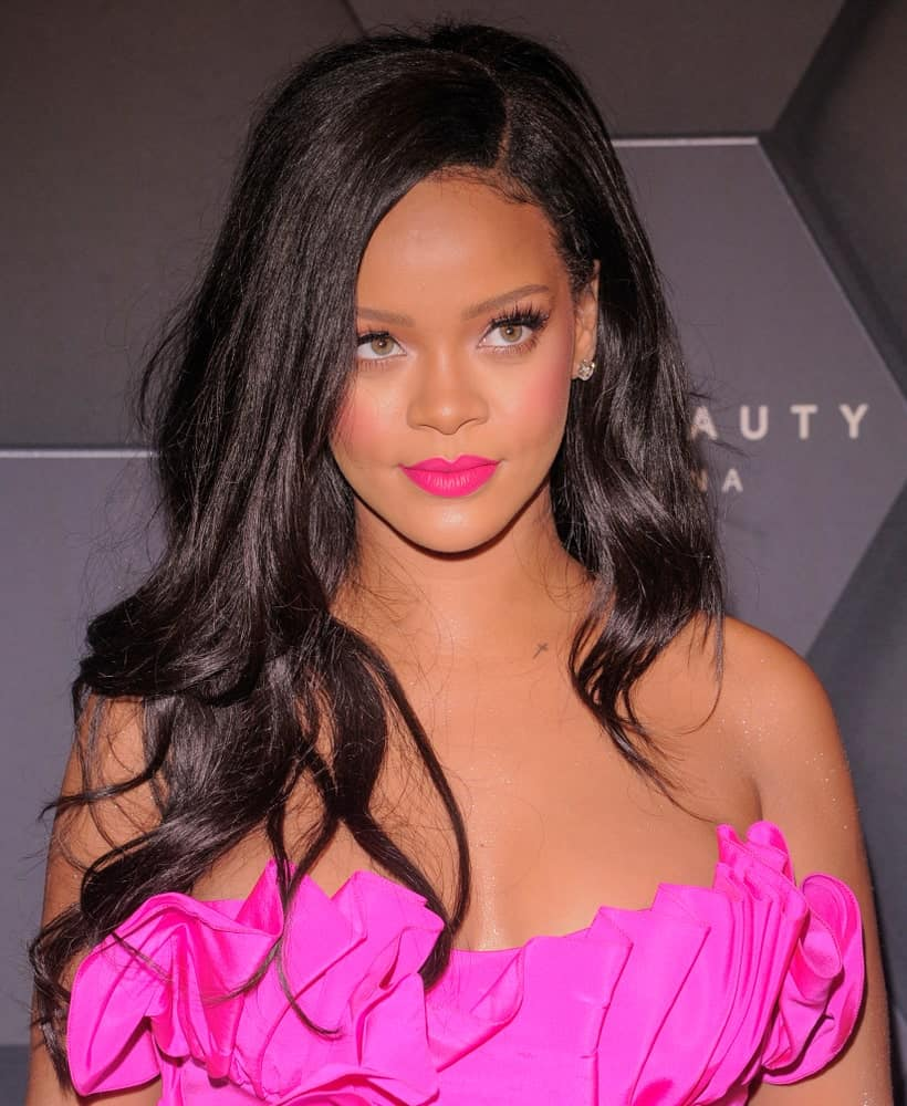 On September 14, 2018, Rihanna looked quite charming in her pink gown by Calvin Klein and her long side-swept wavy dark hairstyle when she attended the Fenty Beauty 1-year anniversary at Sephora inside JCPenney in Brooklyn.