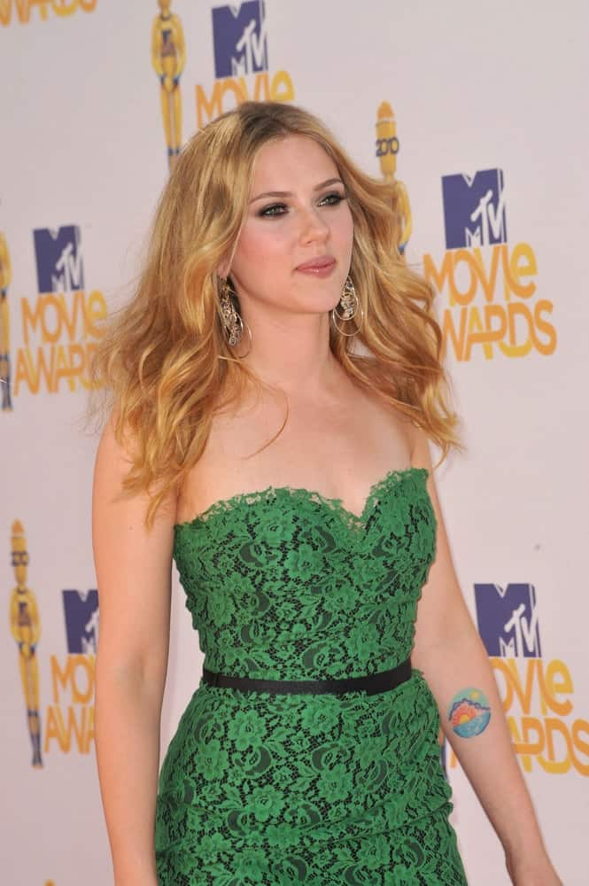 Scarlett Johansson wore a stunning and sexy green embroidered dress with her loose and tousled wavy hair with a sandy blond tone at the 2010 MTV Movie Awards at the Gibson Amphitheatre, Universal Studios in Hollywood on June 6, 2010.