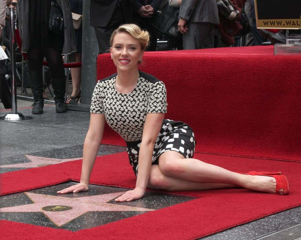 Scarlett Johansson posed with her star wearing a black and white short dress as well as an elegant upstyle with a side-swept finish at her own Walk of Fame Ceremony at Hollywood Boulevard on May 2, 2012 in Los Angeles, CA.