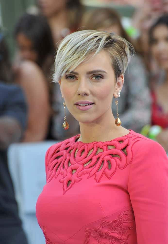 On April 12, 2015, Scarlett Johansson wore a lovely pink dress with fashionable details to pair with her simple make-up and side-swept tousled pixie hairstyle with highlights at the 2015 MTV Movie Awards at the Nokia Theatre LA Live.