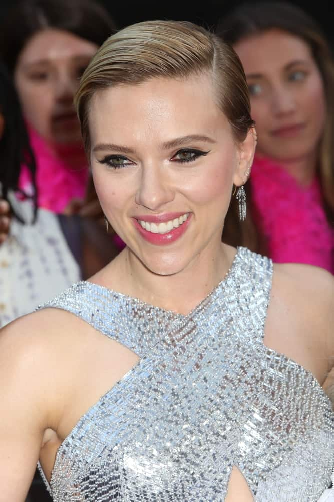 Scarlett Johansson paired her silver shiny dress with a slick side-parted hairstyle to emphasize her lovely smile and earrings at the premiere of