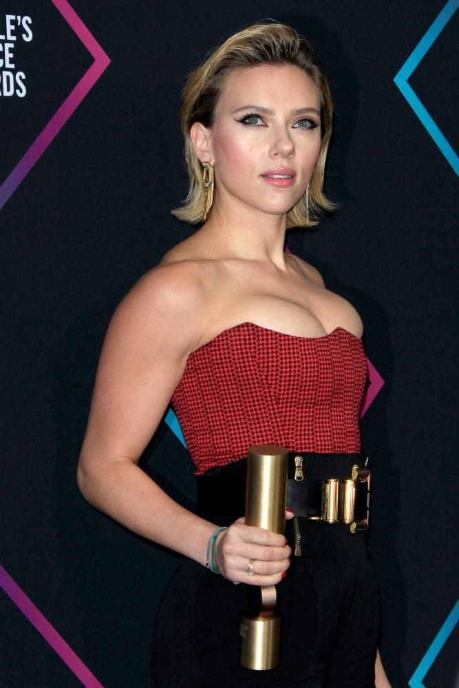 Scarlett Johansson wore a red bustier outfit with her lovely and sexy slick side-swept short bob hairstyle with highlights at the People's Choice Awards 2018 at the Barker Hanger on November 11, 2018 in Santa Monica, CA.