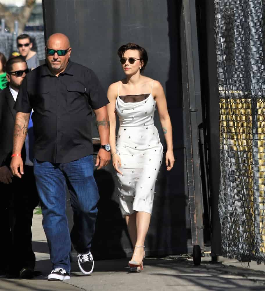 Actress Scarlett Johannson was seen walking to the Jimmy Kimmel studio during the Avengers week on Jimmy Kimmel Live! on April 24, 2018. She wore a white summer dress that she paired with cool sunglasses and a side-swept short dark hairstyle.
