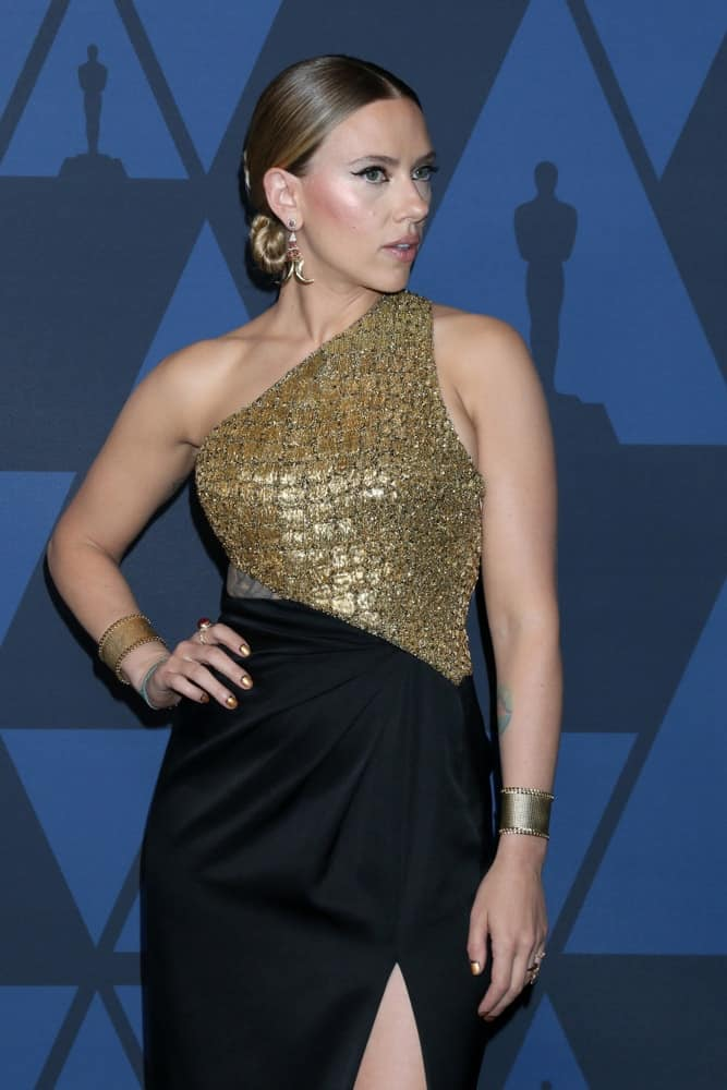 Scarlett Johansson wore a stylish black and gold dress with her fashionable slicked back low bun hairstyle and smoky eyes at the 11th Annual Governors Awards at the Dolby Theater on October 27, 2019 in Los Angeles, CA.