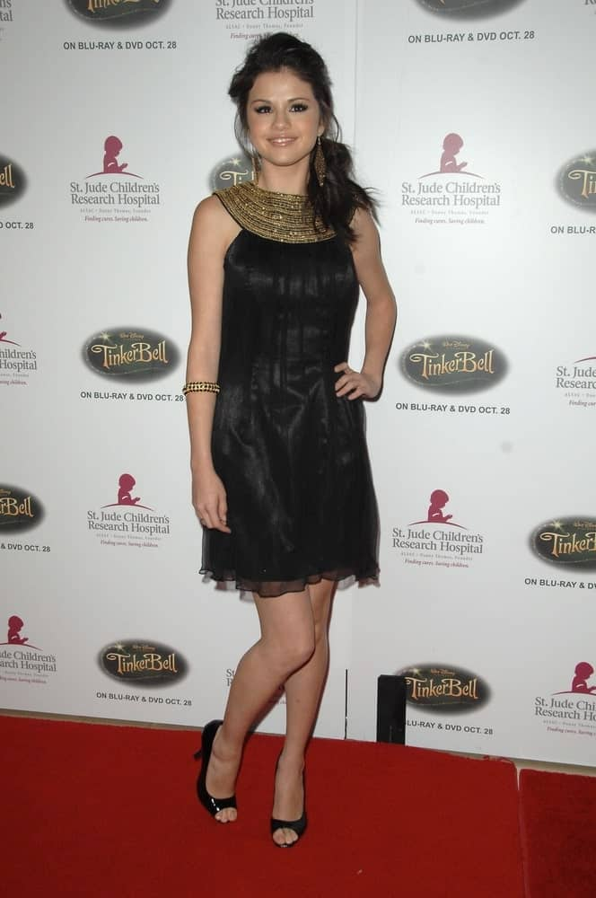 Selena Gomez wore a lovely short black dress with an Egyptian inspiration at the St Jude Children's Research Hospital Runway for Life Benefit, Beverly Hilton Hotel in Los Angeles, CA on October 11, 2008. She paired this with a messy and loose low ponytail with tendrils.