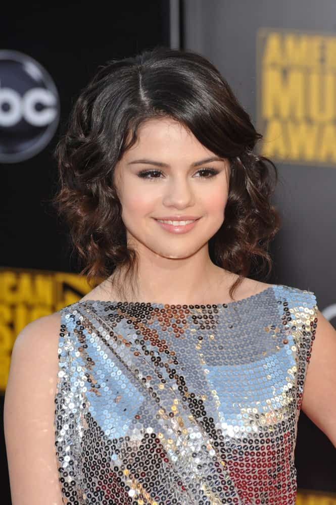 On November 22, 2009, Selena Gomez attended the 2009 American Music Awards at the Nokia Theatre L.A. Live. She wore a fashionable silver sequined dress that went well with her short curly hairstyle that has a slight tousle and long side-swept bangs.