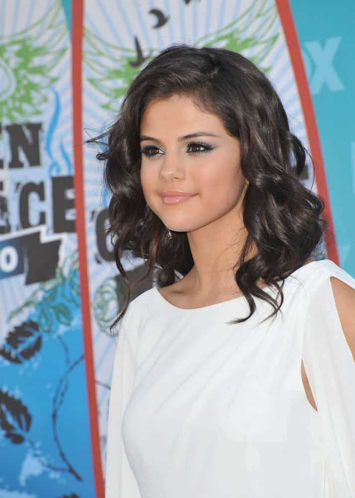 On August 8, 2010, Selena Gomez attended the 2010 Teen Choice Awards at the Gibson Amphitheatre, Universal Studios, Hollywood. She wore a classy white dress that complemented her shoulder-length loose curls with layers.