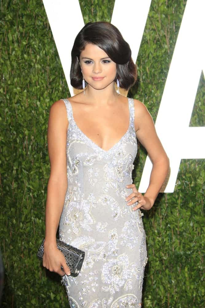 Selena Gomez went for a vintage look to her classy dress and smooth silky hairstyle that has large curls at the shoulders at the Vanity Fair Oscar Party at Sunset Tower on February 26, 2012 in West Hollywood, California.