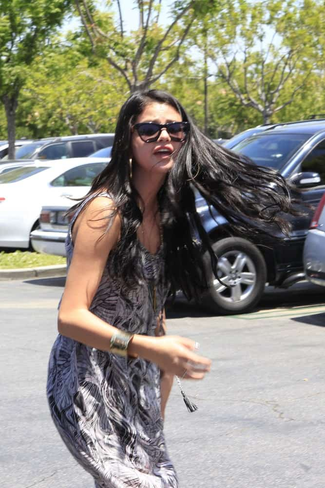Selena Gomez was seen walking to the parking lot of Commons Shopping Center in Calabasas, California on May 27, 2012. She wore a long casual dress that she paired with her long and loose wavy hairstyle.