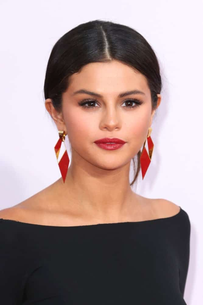 Selena Gomez wore a neat loose bun hairstyle with a simple black outfit and red earrings at the 2014 American Music Awards - Arrivals at the Nokia Theater on November 23, 2014 in Los Angeles, CA.