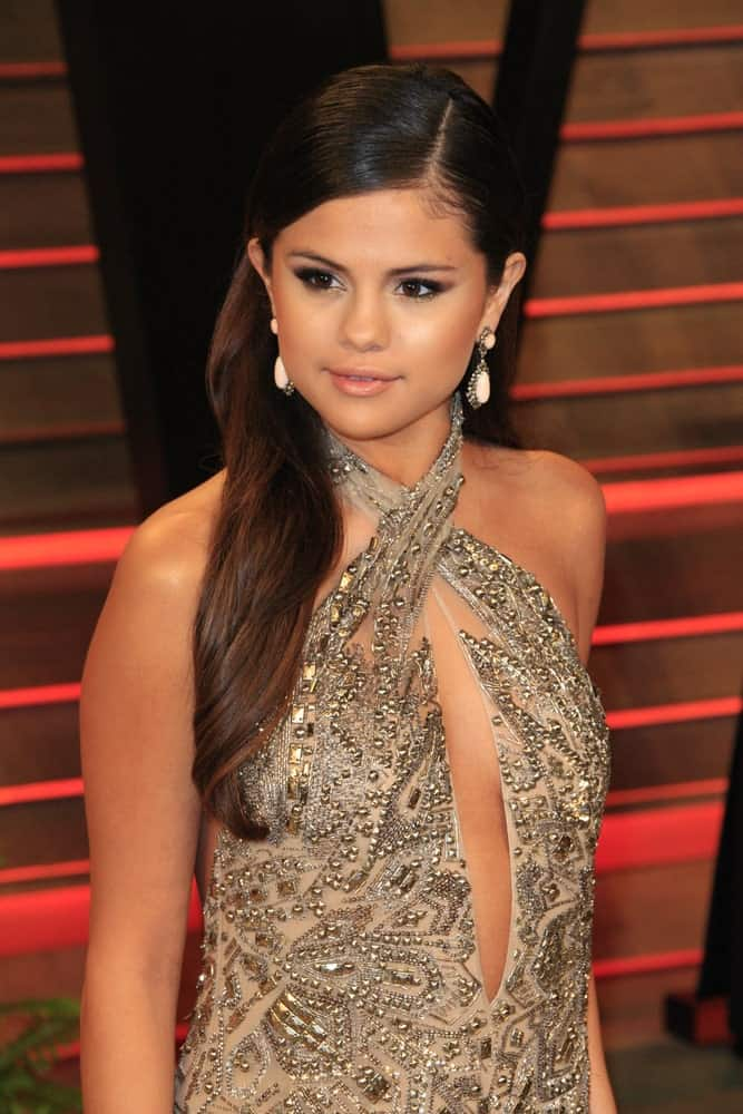 Selena Gomez was at the 2014 Vanity Fair Oscar Party at the Sunset Boulevard on March 2, 2014 in West Hollywood, CA. She looked classy in her detailed sheer dress and side-swept half up hairstyle.