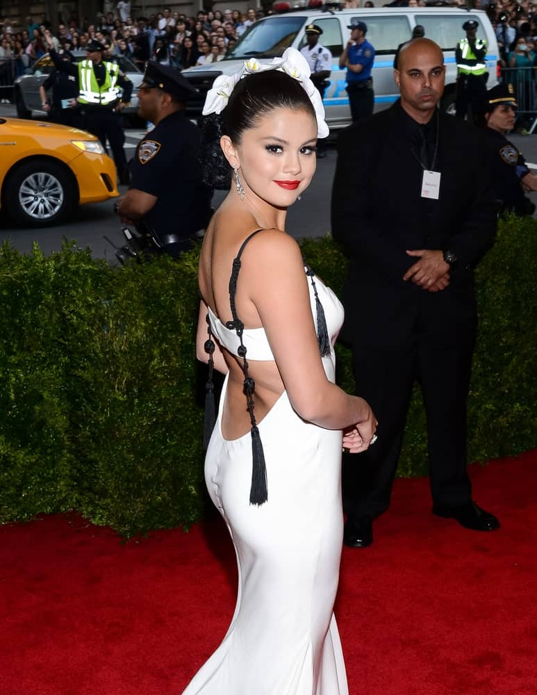 On May 04, 2015, Selena Gomez attended the 'China: Through The Looking Glass' Costume Institute Gala, held at the Metropolitan Museum of Art in New York City, New York. She paired her white dress with a slick bun hairstyle decorated with white flowers.