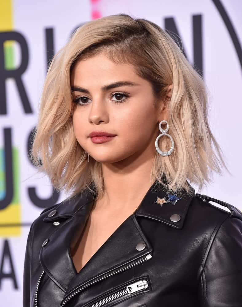 Selena Gomez attended the 2017 American Music Awards on November 19, 2017 in Los Angeles, CA. She paired her cool black leather jacket with a short tousled and wavy platinum blonde hairstyle.