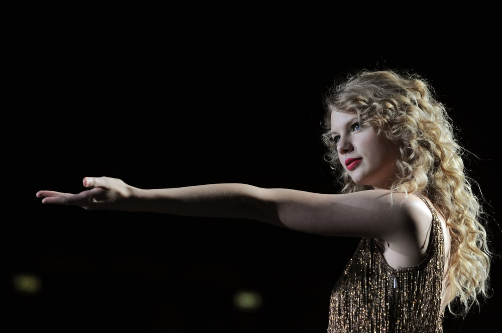 Taylor Swift during her live concert at Forum Assago on March 15, 2011 rocking a long curly hairstyle paired with a sparkling dress.